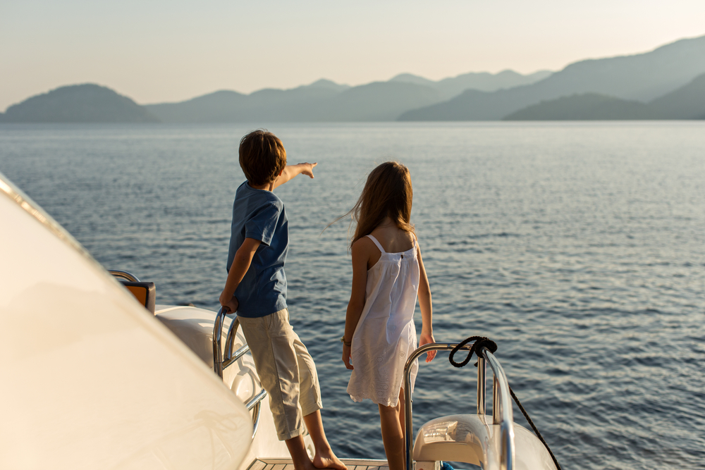 kids on  a boat travel at sea